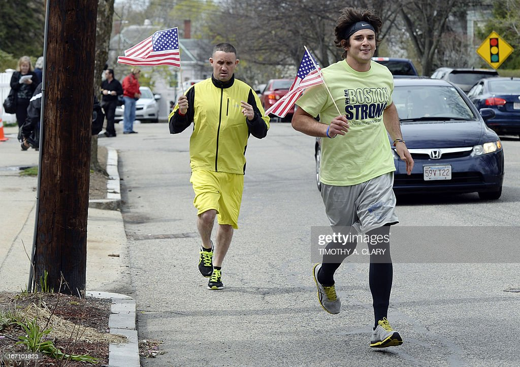 Joggers with US flags run on April 20, 2013 by the street leading to the house where Dzhokhar Tsarnaev was hiding and captured in Watertown, Massachusetts. Thousands of heavily armed police staged an intense manhunt April 29 for the Chechen teenager suspected in the Boston marathon bombings with his brother, who was killed in a shootout. Dzhokhar Tsarnaev, 19, defied the massive force after his 26-year-old brother Tamerlan was shot and suffered critical injuries from explosives believed to have been strapped to his body.
