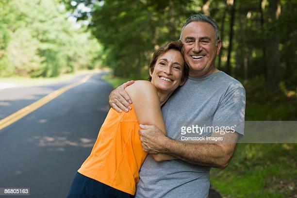 Jogging couple embracing at roadside