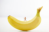 Jogging miniature woman on banana