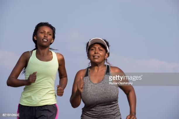 Jogging women running. Female runner and beginner plump woman during an outdoor workout.