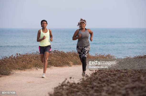 Jogging women running. Female runner and beginner plump woman during an outdoor workout on the coast line.
