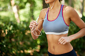 Slim woman jogging with personal stereo