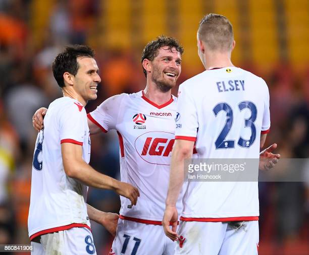 Johan Absalonsen celebrates with Isaias and Jordan Elsey of Adelaide United after winning the round two ALeague match between the Brisbane Roar and...