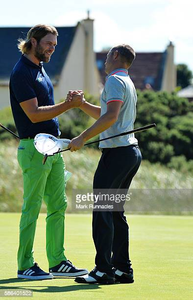 Johan Carlsson of Sweden and Alex Noren of Sweden shake hands on the green of hole 16 after Noren won their match on day three of the Aberdeen Asset...