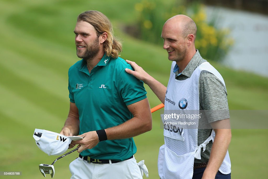 Johan Carlsson of Sweden leaves the 18th green with his caddie during day three of the BMW PGA Championship at Wentworth on May 28, 2016 in Virginia Water, England.