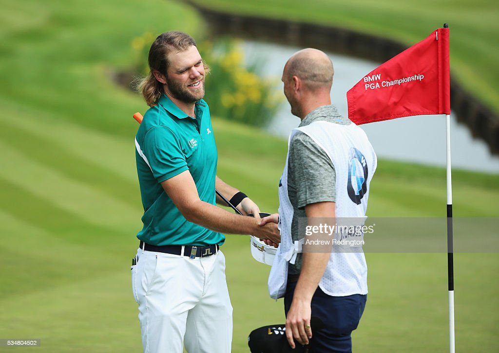 Johan Carlsson of Sweden shakes hands with his caddie on the 18th green during day three of the BMW PGA Championship at Wentworth on May 28, 2016 in Virginia Water, England.