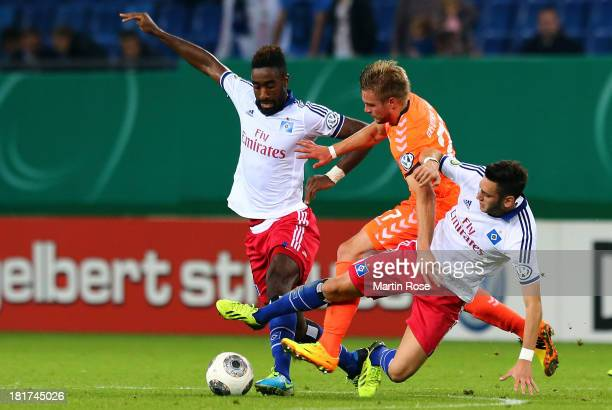 Johan Djourou and Hakan Calhanoglu of Hamburg and Florian Trinks of Greuther Fuerth battle for the ball during the DFB Cup second round match between...