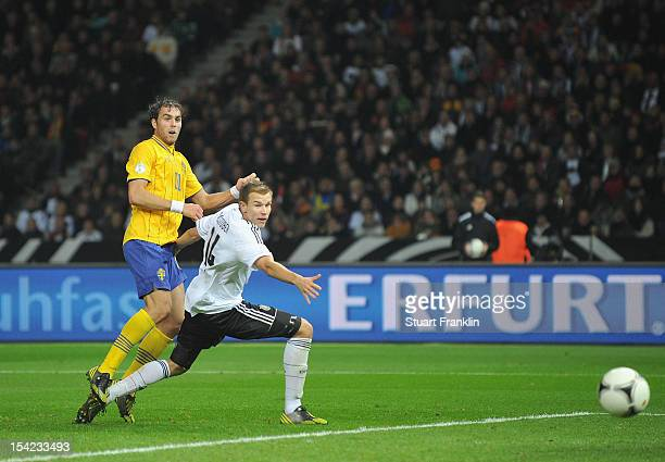 Johan Elmander of Sweden knocks the ball past Holger Badstuber to score the third goal during the FIFA 2014 World Cup qualifier group C match between...