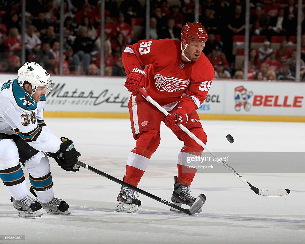 <a gi-track='captionPersonalityLinkClicked' href=/galleries/search?phrase=Johan+Franzen&family=editorial&specificpeople=624356 ng-click='$event.stopPropagation()'>Johan Franzen</a> #93 of the Detroit Red Wings and <a gi-track='captionPersonalityLinkClicked' href=/galleries/search?phrase=Logan+Couture&family=editorial&specificpeople=809700 ng-click='$event.stopPropagation()'>Logan Couture</a> #39 of the San Jose Sharks battle for the puck during a NHL game at Joe Louis Arena on April 11, 2013 in Detroit, Michigan.
