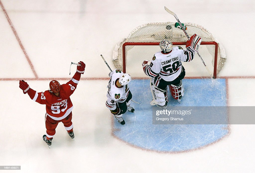 <a gi-track='captionPersonalityLinkClicked' href=/galleries/search?phrase=Johan+Franzen&family=editorial&specificpeople=624356 ng-click='$event.stopPropagation()'>Johan Franzen</a> #93 of the Detroit Red Wings celebrates a third period goal by teammate Pavel Datsyuk #13 next to <a gi-track='captionPersonalityLinkClicked' href=/galleries/search?phrase=Corey+Crawford&family=editorial&specificpeople=818935 ng-click='$event.stopPropagation()'>Corey Crawford</a> #50 and <a gi-track='captionPersonalityLinkClicked' href=/galleries/search?phrase=Michal+Rozsival&family=editorial&specificpeople=216462 ng-click='$event.stopPropagation()'>Michal Rozsival</a> #32 of the Chicago Blackhawks in Game Three of the Western Conference Semifinals during the 2013 NHL Stanley Cup Playoffs at Joe Louis Arena on May 20, 2013 in Detroit, Michigan. Detroit won the game 3-1 to take a 2-1 series lead.
