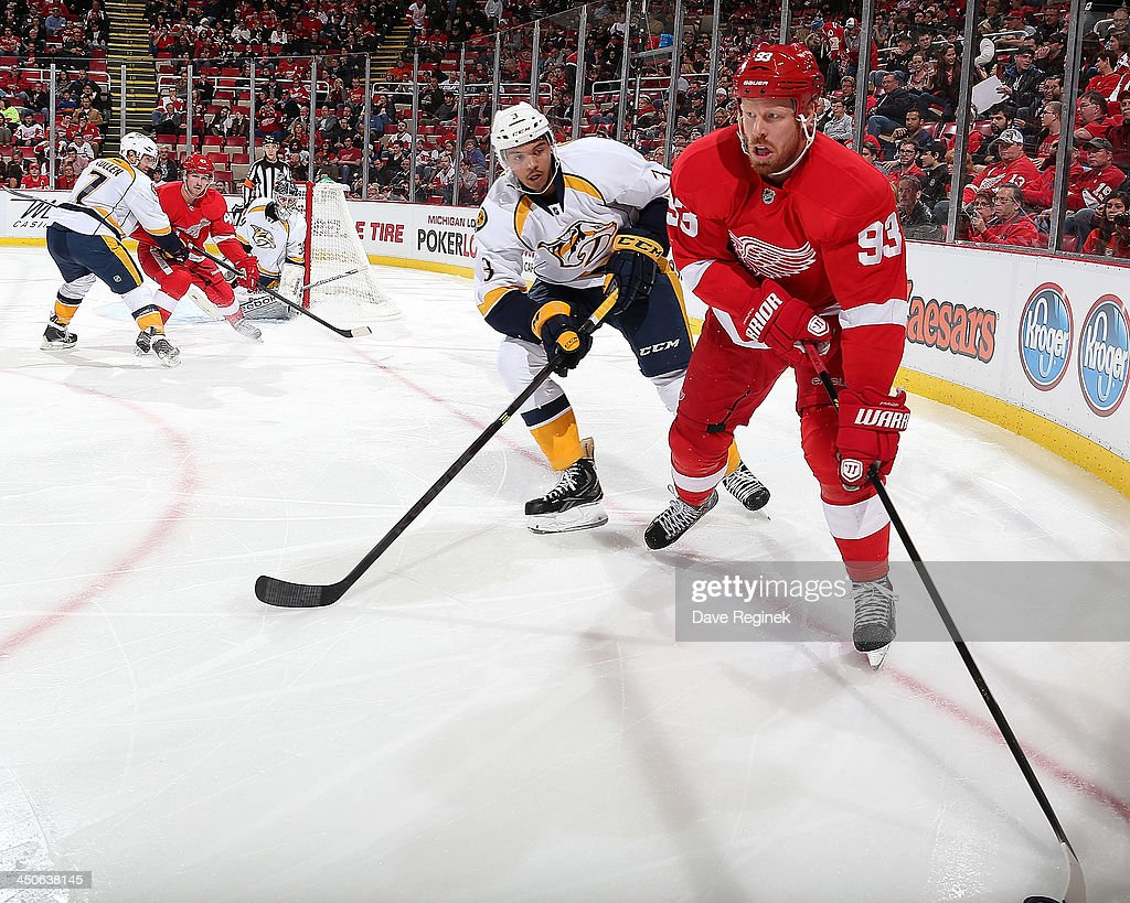 Johan Franzen #93 of the Detroit Red Wings handles the puck in the corner as Seth Jones #3 of the Nashville Predators defends him during an NHL game at Joe Louis Arena on November 19, 2013 in Detroit, Michigan.