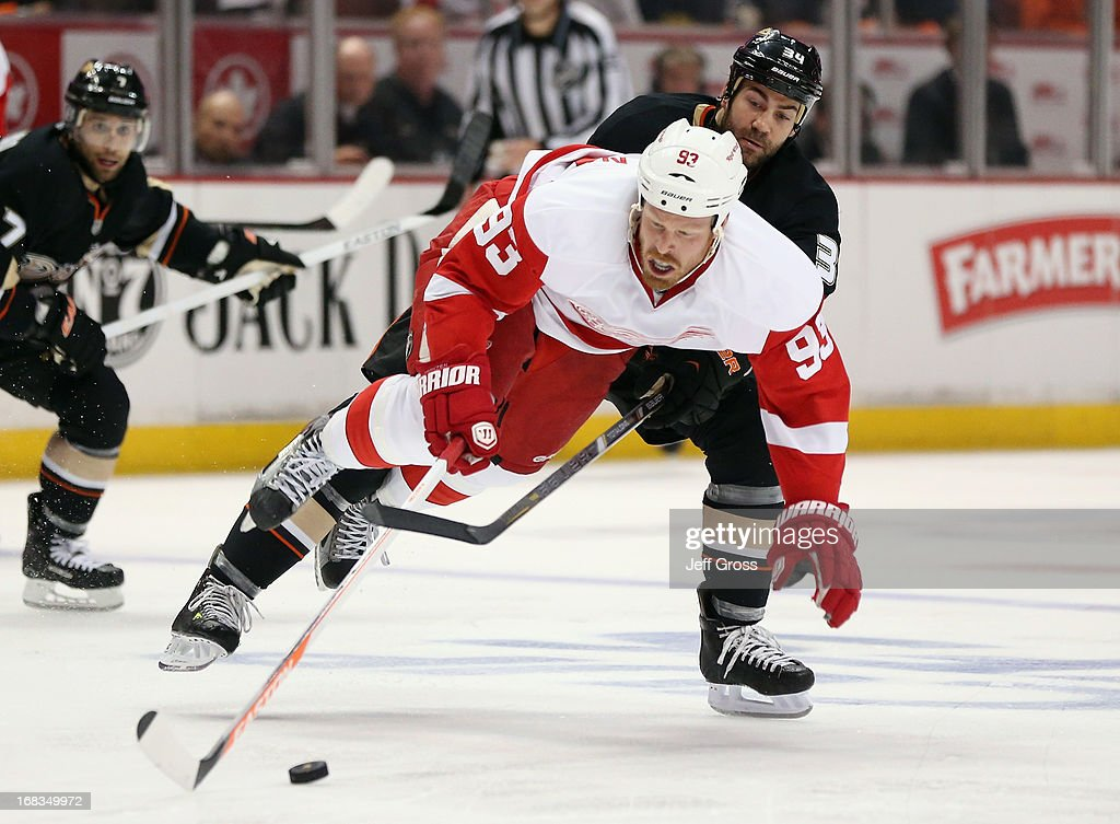 <a gi-track='captionPersonalityLinkClicked' href=/galleries/search?phrase=Johan+Franzen&family=editorial&specificpeople=624356 ng-click='$event.stopPropagation()'>Johan Franzen</a> #93 of the Detroit Red Wings is brought down by <a gi-track='captionPersonalityLinkClicked' href=/galleries/search?phrase=Daniel+Winnik&family=editorial&specificpeople=2529214 ng-click='$event.stopPropagation()'>Daniel Winnik</a> #34 of the Anaheim Ducks in the second period in Game Five of the Western Conference Quarterfinals during the 2013 NHL Stanley Cup Playoffs at Honda Center on May 8, 2013 in Anaheim, California. The Ducks defeated the Red Wings 3-2 in overtime.