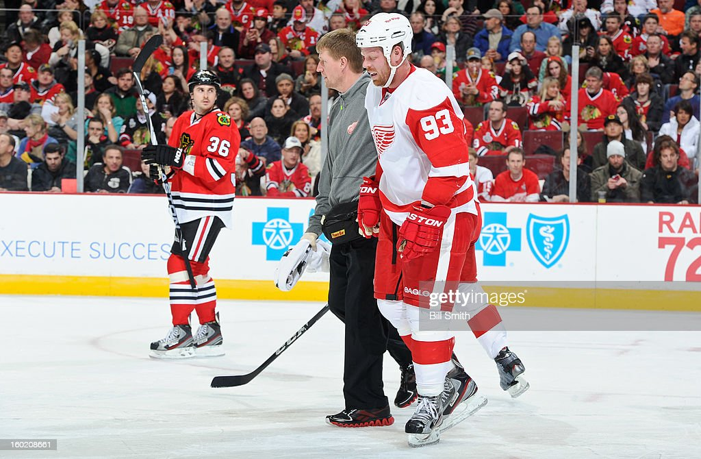 Johan Franzen #93 of the Detroit Red Wings is helped off the ice by head athletic trainer Piet Van Zant during the NHL game against the Chicago Blackhawks on January 27, 2013 at the United Center in Chicago, Illinois.