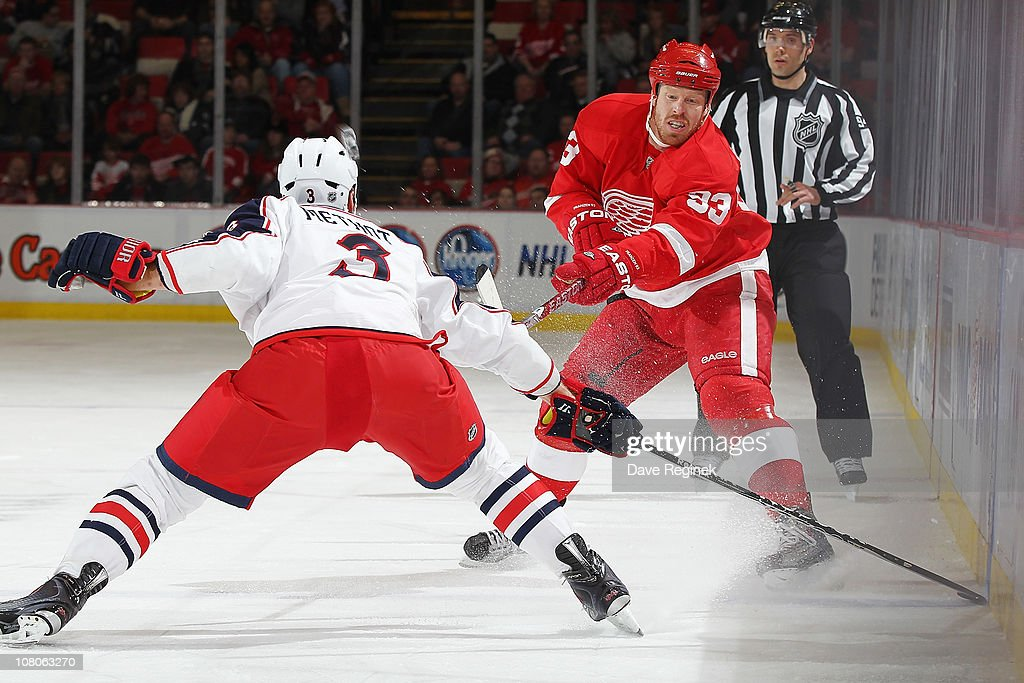 <a gi-track='captionPersonalityLinkClicked' href=/galleries/search?phrase=Johan+Franzen&family=editorial&specificpeople=624356 ng-click='$event.stopPropagation()'>Johan Franzen</a> #93 of the Detroit Red Wings makes a pass in front of <a gi-track='captionPersonalityLinkClicked' href=/galleries/search?phrase=Marc+Methot&family=editorial&specificpeople=2216900 ng-click='$event.stopPropagation()'>Marc Methot</a> #3 of the Columbus Blue Jackets during an NHL game at Joe Louis Arena on January 15, 2011 in Detroit, Michigan.