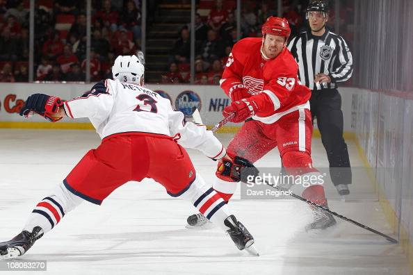 Johan Franzen of the Detroit Red Wings makes a pass in front of Marc Methot of the Columbus Blue Jackets during an NHL game at Joe Louis Arena on...
