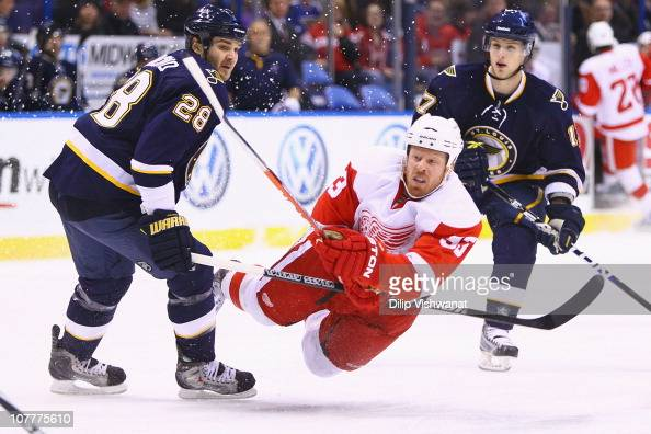 Johan Franzen of the Detroit Red Wings shoots the puck against Carlo Colaiacovo and Vladimir Sobotka both of the St Louis Blues at the Scottrade...