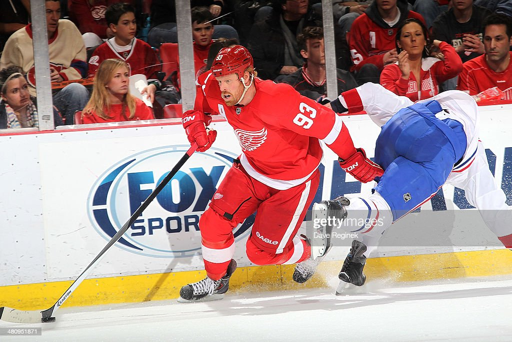 <a gi-track='captionPersonalityLinkClicked' href=/galleries/search?phrase=Johan+Franzen&family=editorial&specificpeople=624356 ng-click='$event.stopPropagation()'>Johan Franzen</a> #93 of the Detroit Red Wings side steps <a gi-track='captionPersonalityLinkClicked' href=/galleries/search?phrase=Jarred+Tinordi&family=editorial&specificpeople=7029368 ng-click='$event.stopPropagation()'>Jarred Tinordi</a> #24 of the Montreal Canadiens during an NHL game on March 27, 2014 at Joe Louis Arena in Detroit, Michigan.