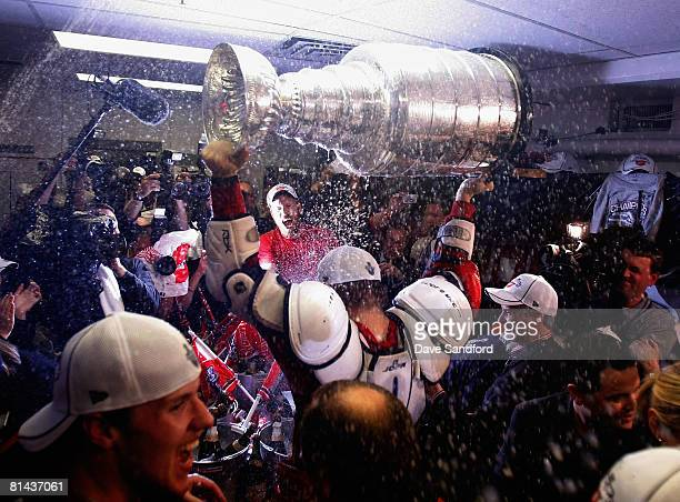 Johan Franzen of the Detroit Red Wings sprays teammates with champagne as they celebrate with the Stanley Cup in the locker room after defeating the...