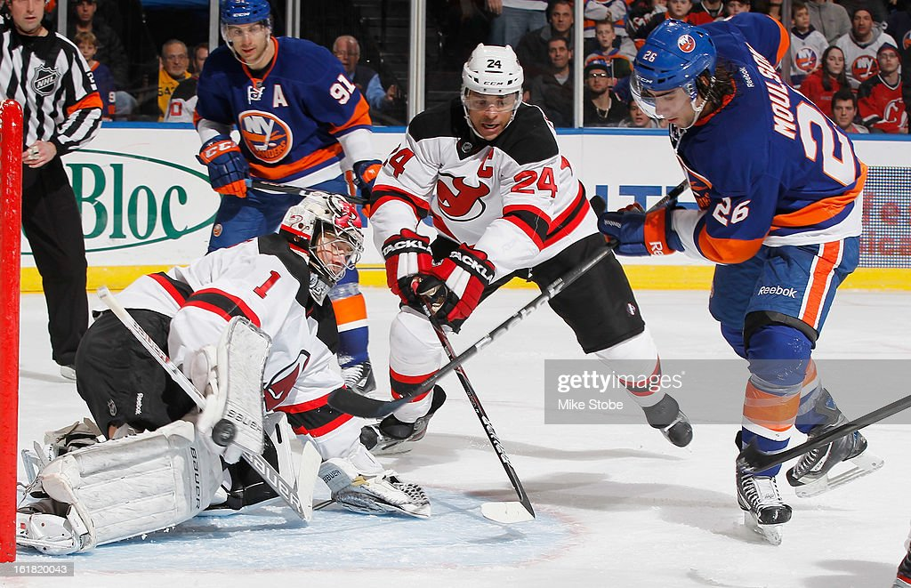 Johan Hedberg #1 and Bryce Salvador #24 of the New Jersey Devils protect the net in front of Matt Moulson #26 of the New York Islanders at Nassau Veterans Memorial Coliseum on February 16, 2013 in Uniondale, New York. The Islanders defeated the Devils 5-1.
