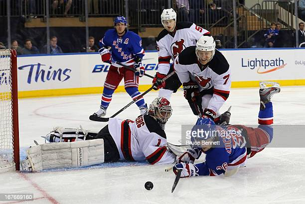 Johan Hedberg and Henrik Tallinder of the New Jersey Devils defend against Mats Zuccarello of the New York Rangers at Madison Square Garden on April...