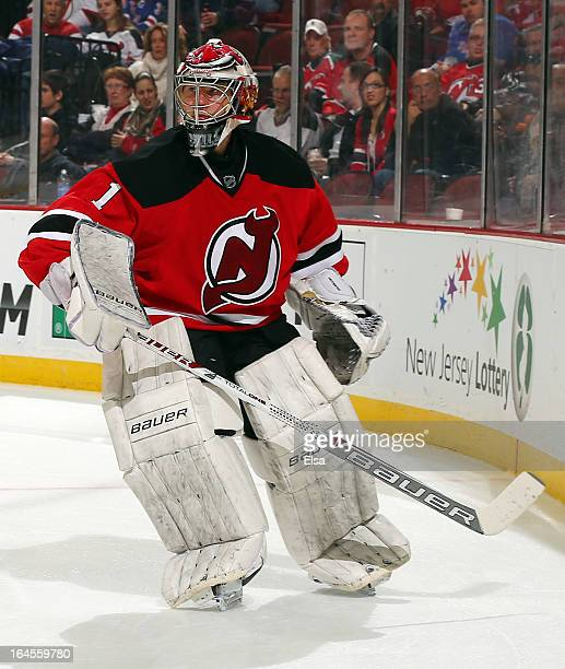 Johan Hedberg of the New Jersey Devils clears the puck behind the net against the New York Rangers at the Prudential Center on March 19 2013 in...