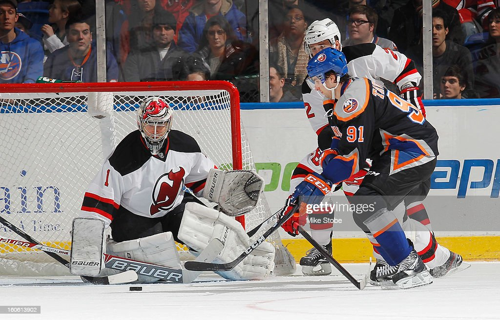 Johan Hedberg #1 of the New Jersey Devils defends the net against John Tavares #91 of the New York Islanders at Nassau Veterans Memorial Coliseum on Febuary 3, 2013 in Uniondale, New York.