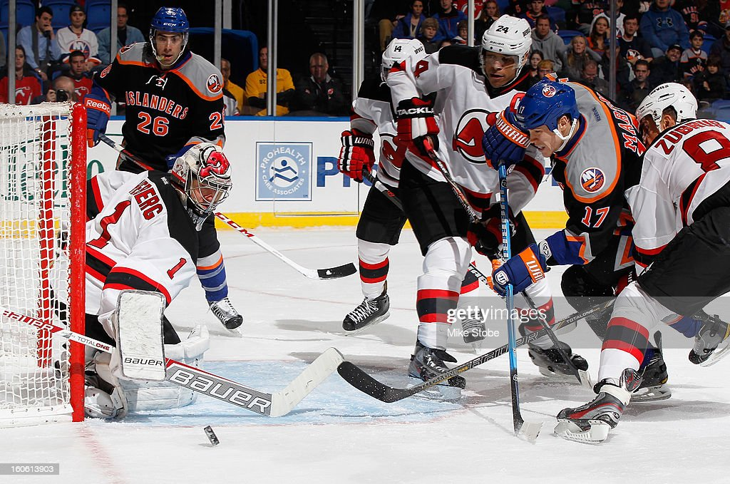 Johan Hedberg #1 of the New Jersey Devils defends the net against Matt Martin #17 of the New York Islanders at Nassau Veterans Memorial Coliseum on Febuary 3, 2013 in Uniondale, New York. The Devils defeat the Islanders 3-0.