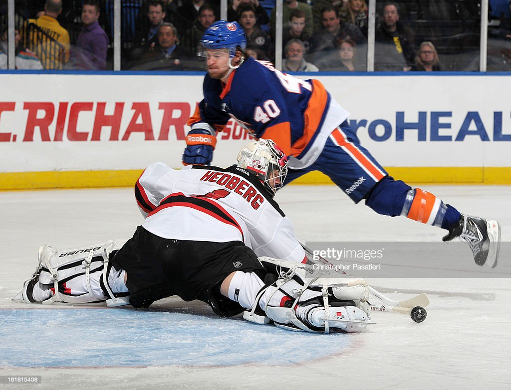 Johan Hedberg #1 of the New Jersey Devils makes a save on a shot on goal by Michael Grabner #40 of the New York Islanders during the game on February 16, 2013 at Nassau Veterans Memorial Coliseum in Uniondale, New York.