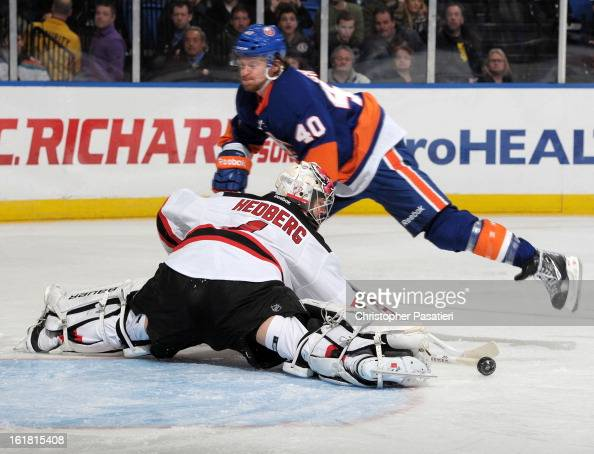Johan Hedberg of the New Jersey Devils makes a save on a shot on goal by Michael Grabner of the New York Islanders during the game on February 16...