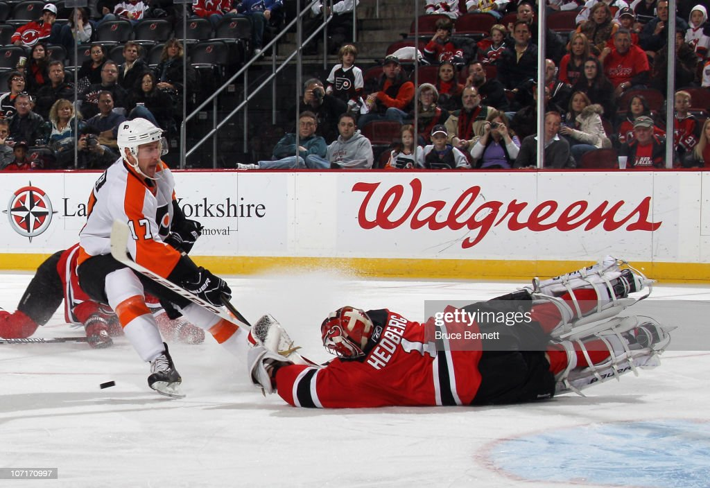 Johan Hedberg of the New Jersey Devils makes a third period save against Jeff Carter of the Philadelphia Flyers at the Prudential Center on November...
