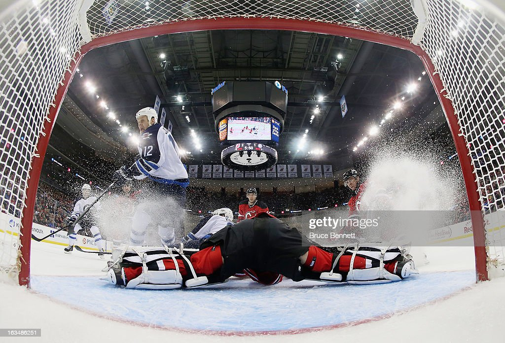 <a gi-track='captionPersonalityLinkClicked' href=/galleries/search?phrase=Johan+Hedberg&family=editorial&specificpeople=202078 ng-click='$event.stopPropagation()'>Johan Hedberg</a> #1 of the New Jersey Devils makes the split save as <a gi-track='captionPersonalityLinkClicked' href=/galleries/search?phrase=Olli+Jokinen&family=editorial&specificpeople=202946 ng-click='$event.stopPropagation()'>Olli Jokinen</a> #12 of the Winnipeg Jets looks for a rebound at the Prudential Center on March 10, 2013 in Newark, New Jersey. The Devils defeated the Jets 3-2 in the shootout.