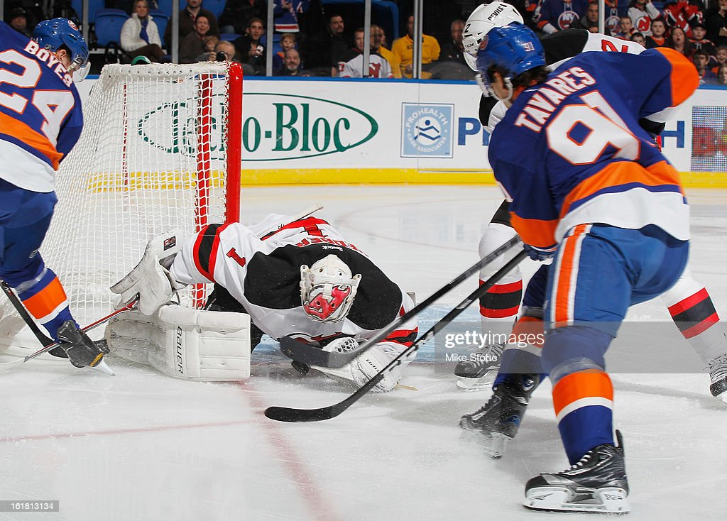 Johan Hedberg #1 of the New Jersey Devils protects the net in front of John Tavares #91 of the New York Islanders at Nassau Veterans Memorial Coliseum on February 16, 2013 in Uniondale, New York.