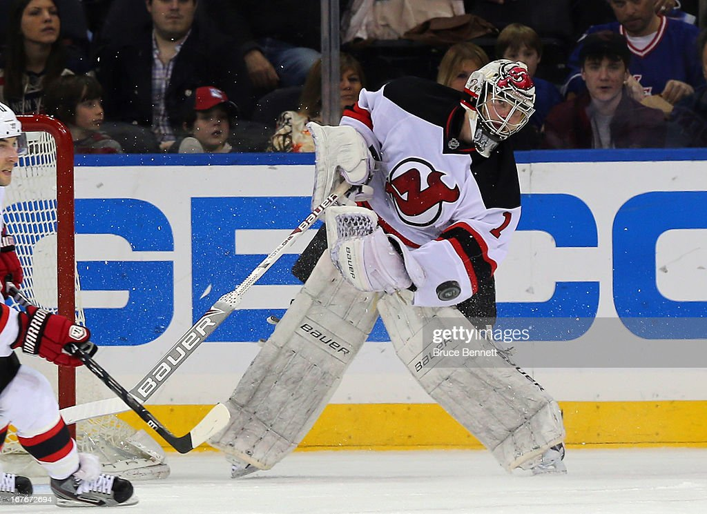Johan Hedberg of the New Jersey Devils shoots the puck out of his own zone in the game against the New York Rangers at Madison Square Garden on April...
