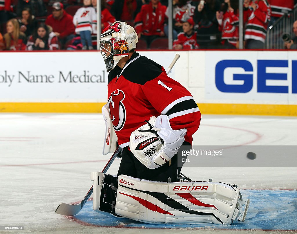 Johan Hedberg of the New Jersey Devils stops shots during warm ups before the game against the Washington Capitals at the Prudential Center on...