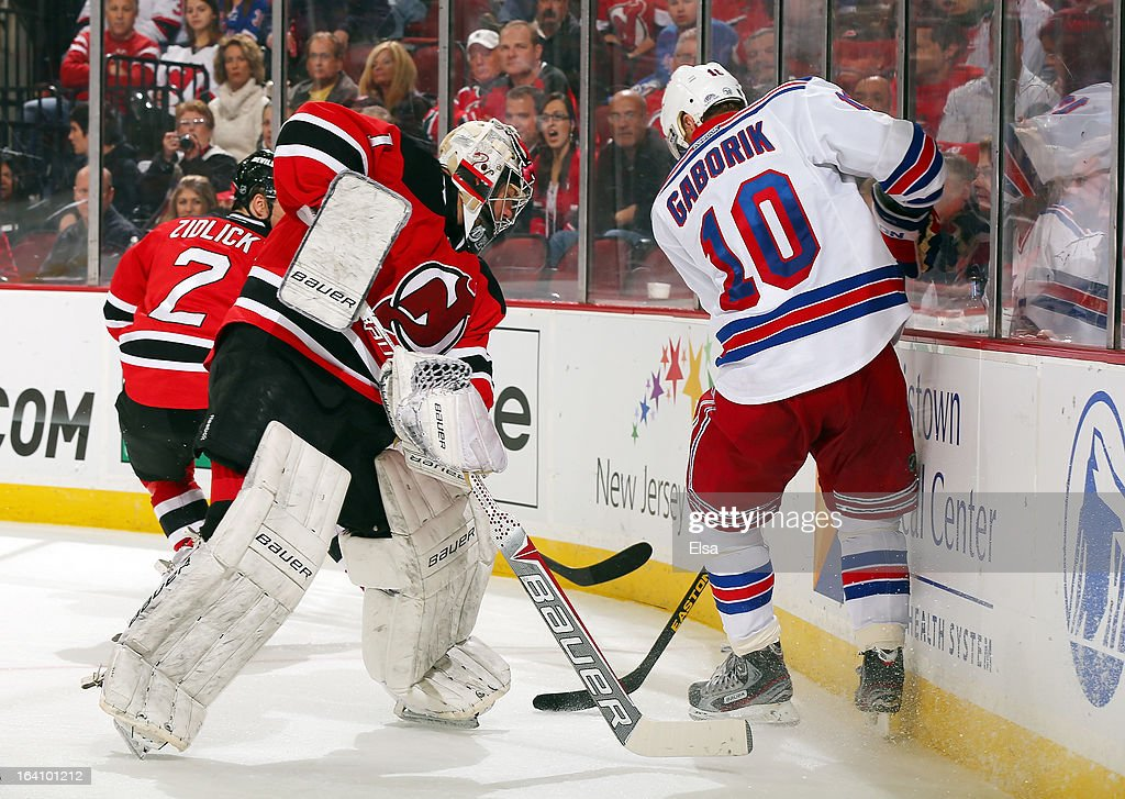 Johan Hedberg #1 of the New Jersey Devils tries to play the puck as Marian Gaborik #10 of the New York Rangers tries to make the steal at the Prudential Center on March 19, 2013 in Newark, New Jersey. The New York Rangers defeated the New Jersey Devils 3-2.