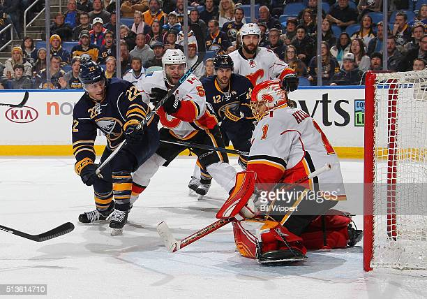 Johan Larsson of the Buffalo Sabres backhands the puck over Jonas Hiller of the Calgary Flames to score a third period goal during an NHL game on...