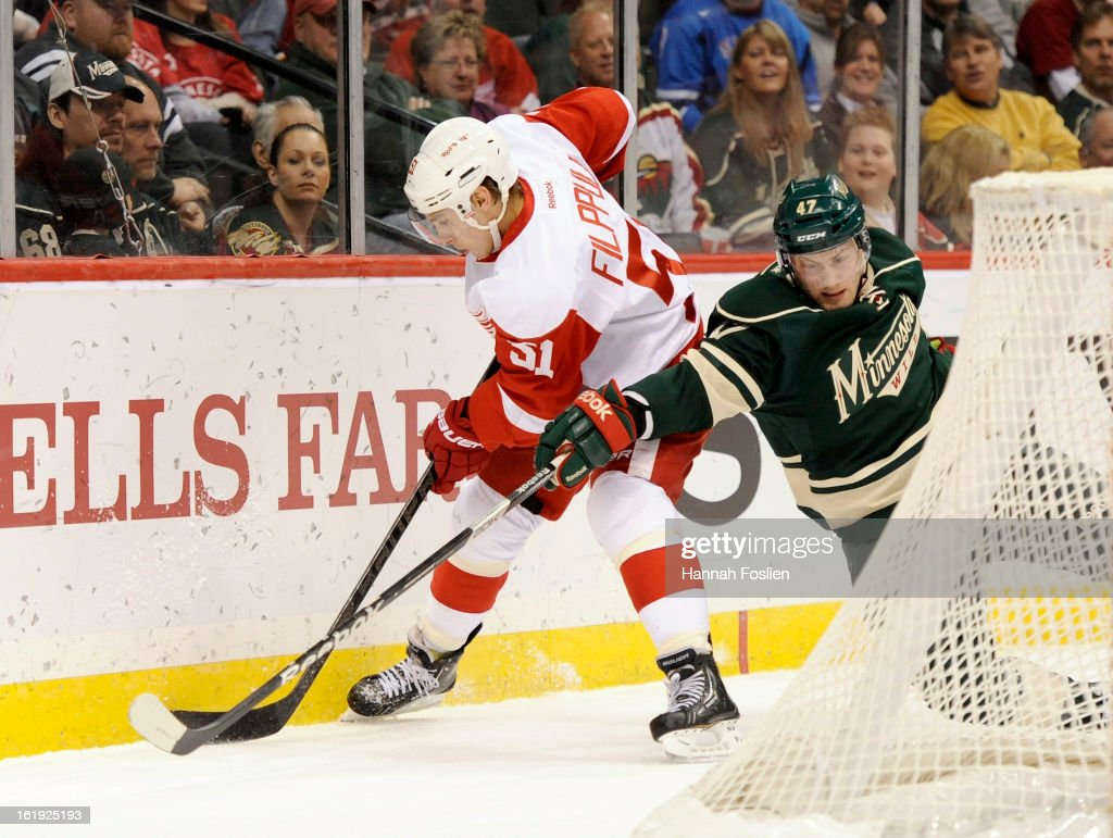 Johan Larsson #47 of the Minnesota Wild attempts to get the puck away from Valtteri Filppula #51 of the Detroit Red Wings during the first period of the game on February 17, 2013 at Xcel Energy Center in St Paul, Minnesota.