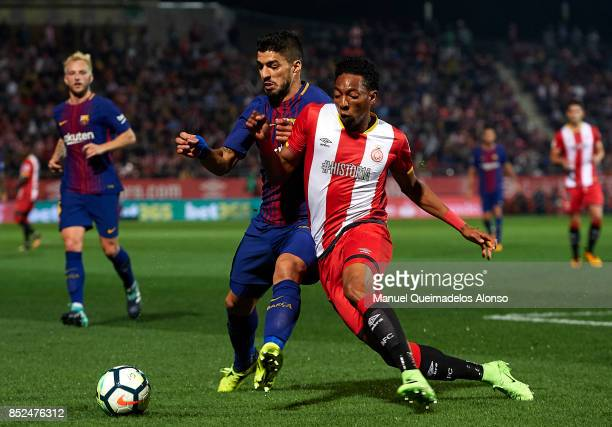 Johan Mojica of Girona competes for the ball with Luis Suarez of Barcelona during the La Liga match between Girona and Barcelona at Municipal de...