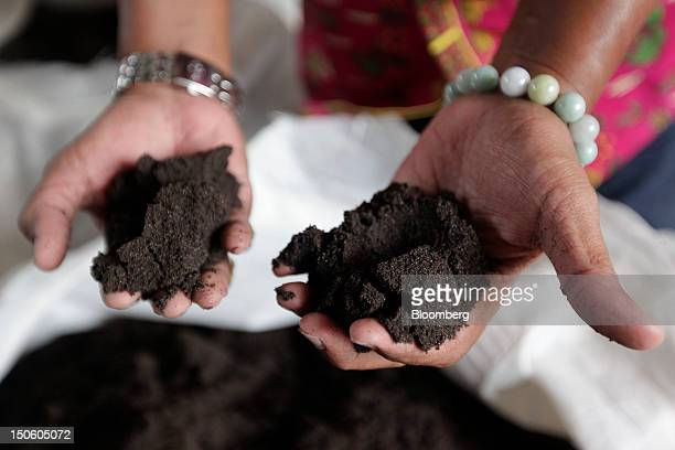Johan Murod a private tin refiner holds samples of tin ore for a photograph at his smelter in Pangkal Pinang Bangka Island Indonesia on Thursday July...