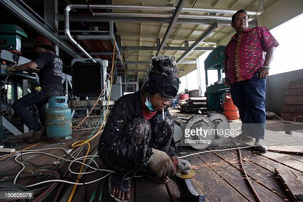 Johan Murod a private tin refiner right stands for a photograph as his employees work on his dredging ship in Pangkal Pinang Bangka Island Indonesia...
