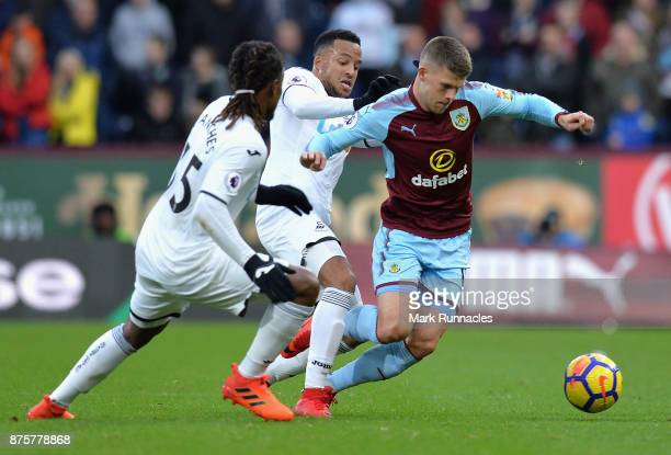 Johann Gudmundsson of Burnley competes for the ball against Jordan Ayew and Renato Sanches of Swansea City during the Premier League match between...