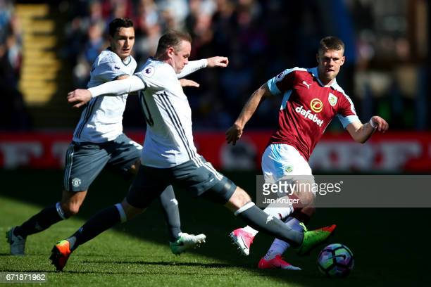 Johann Gudmundsson of Burnley passes the ball under pressure from Wayne Rooney of Manchester United during the Premier League match between Burnley...
