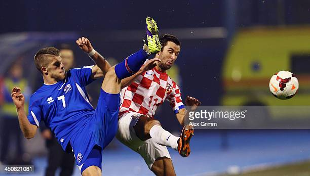 Johann Gudmundsson of Iceland is challenged by Darijo Srna of Croatia during the FIFA 2014 World Cup Qualifier playoff second leg match between...