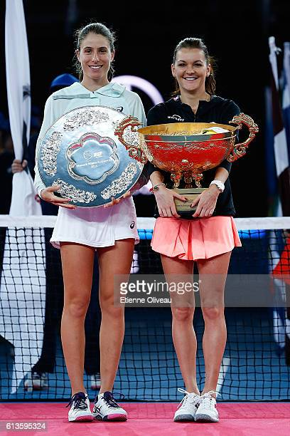 Johanna Konta of Great Britain holds the runner up trophy next to Agnieszka Radwanska of Poland who holds the winners trophy after the Women's...