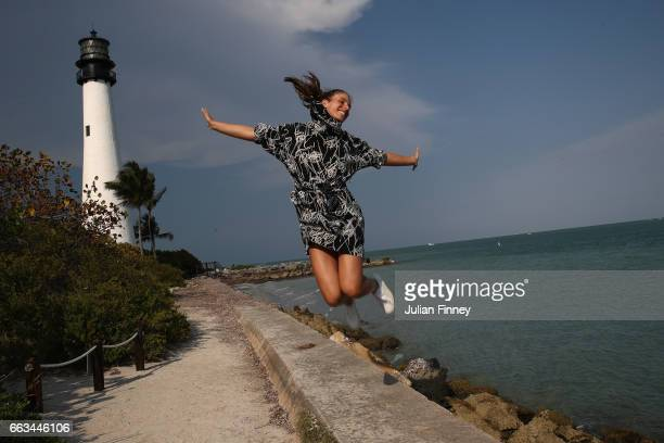 Johanna Konta of Great Britain jumps in the air next to a lighthouse during a photo shoot after she defeated Caroline Wozniacki of Denmark in the...