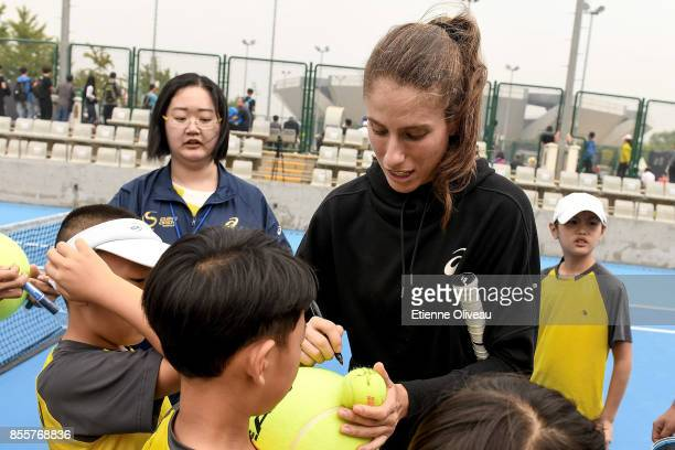 Johanna Konta of Great Britain signs autographs during the event 'Tennis into Campus' during day 1 of the 2017 China Open at the China National...