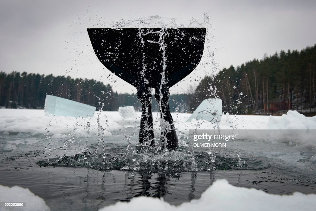 Johanna Nordblad, 42, Finnish freediver duck-dives during an Ice-freediving training session on February 28, 2017, in Somero (southwest Finland). The ice is about 45cm thick, water temperature +1°C. Johanna Nordblad holds the world record of freediving under ice with bathing suit with 50m distance. / AFP PHOTO / OLIVIER MORIN / TO GO WITH AFP STORY BY Sabine COLPART