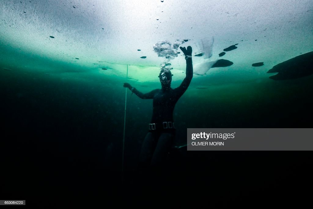 Johanna Nordblad, 42, Finnish freediver swims under ice during a Ice-freediving training session on February 28, 2017, in Somero (southwest Finland). The ice is about 45cm thick, water temperature +1°C. Johanna Nordblad holds the world record of freediving under ice with bathing suit with 50m distance. / AFP PHOTO / OLIVIER MORIN / TO GO WITH AFP STORY BY Sabine COLPART
