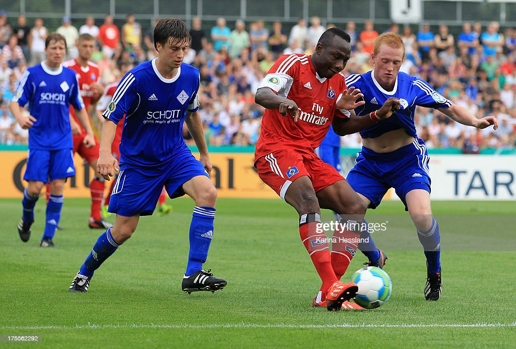 Johannes Carl and Christian Kretzer of Jena and Jacques Daogari Zoua of Hamburg battle for the ball during the DFB Cup between SV Schott Jena and Hamburger SV at Ernst-Abbe-Sportfeld on August 04, 2013 in Jena,Germany.