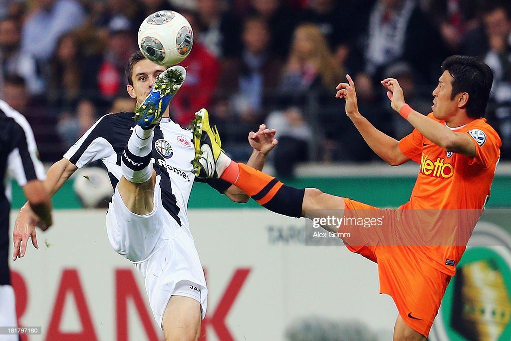 Johannes Flum (L) of Frankfurt is challenged by Yusuke Tasaka of Bochum during the DFB Cup second round match between Eintracht Frankfurt and VfL Bochum at Commerzbank-Arena on September 25, 2013 in Frankfurt am Main, Germany.